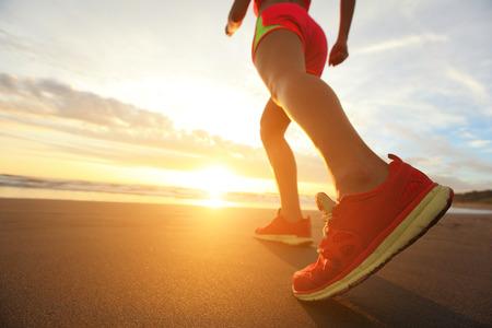 Woman Runner feet running on the beach at sunrise closeup on shoe. woman fitness sunrise jog workout welness concept. asian