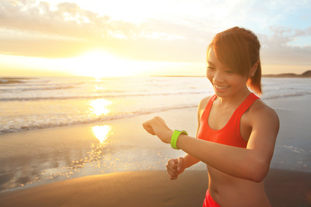 hands free device: Health sport young woman run and look wear smart watch device with touchscreen on the beach at sunrise, asian