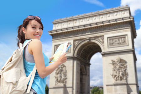 Happy woman travel in Paris, Arc de Triomphe , she look map with sky background photo