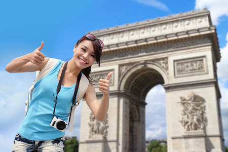 Happy woman travel in Paris, Arc de Triomphe , Cheerful smile woman tourist show thumbs up success sign photo
