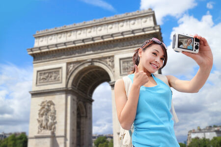 triumphe: Happy woman travel in Paris, Arc de Triomphe , she take photo and selfie by camera