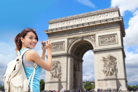 Happy woman travel in Paris, Arc de Triomphe , she take photo by camera photo