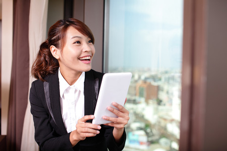Young business travel woman using digital tablet and smart phone in her hotel room, asian Stock Photo