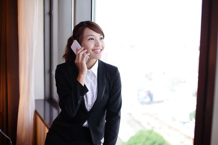 Young business travel woman speaking smart phone in her hotel room, asian photo