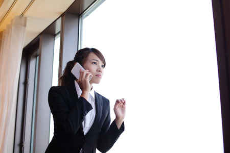 business traveller: Young business travel woman using smart phone in her hotel room, asian