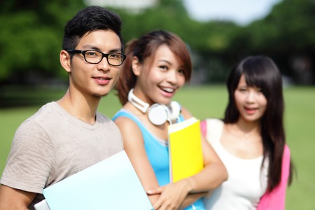 Happy College student man smile to you on campus lawn, asian photo