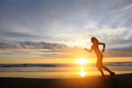 young woman running on the beach at sunrise, asian photo