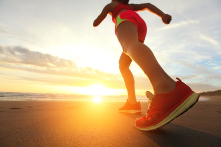Woman Runner feet running on the beach at sunrise closeup on shoe. woman fitness sunrise jog workout welness concept. asian