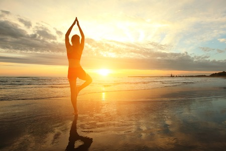 Silhueta de mulher praticando yoga na praia do mar ao pôr do sol