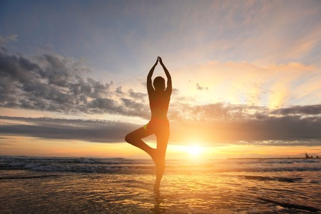 Young woman silhouette practicing yoga on the sea beach at sunset photo