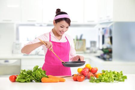 utensilios de cocina: Mujer sonriente feliz en la cocina con productos vegetales frescos que se preparan para una comida saludable, asiático