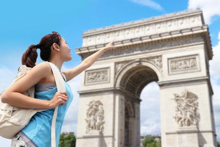 Happy woman travel in Paris, Arc de Triomphe , she finger point the building photo