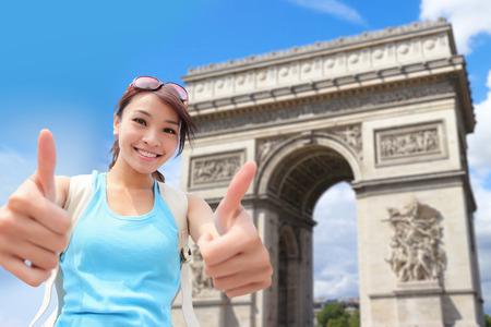 triumphe: Happy woman travel in Paris, Arc de Triomphe , she show thumb up
