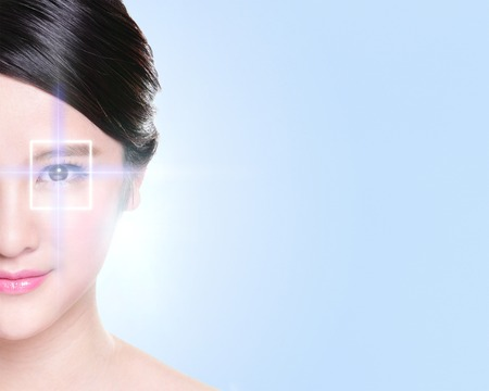 young eyes: Close up portrait of young and beautiful woman eye with the virtual hologram on her eyes, laser medicine and security technology concept, asian