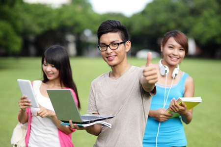 Happy College student man smile and show thumb up to you on campus lawn, asian photo