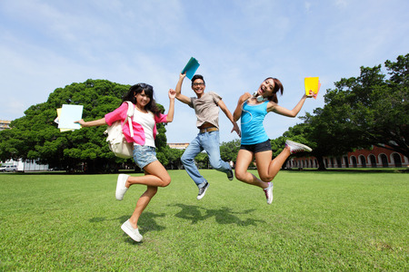 Happy College students jump and smile to you on campus lawn, asian Stock Photo