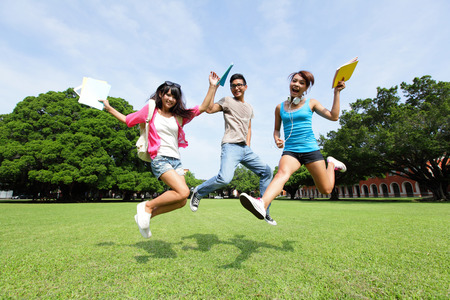 college: Happy College students jump and smile to you on campus lawn, asian Stock Photo
