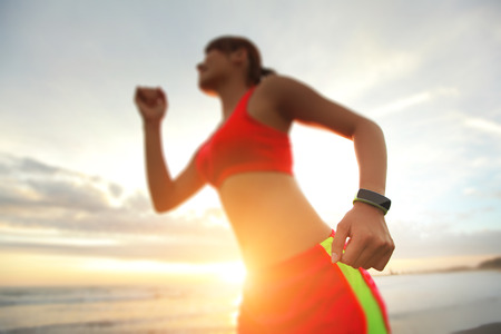 Health sport young woman run and wear smart watch device ( focus on watch ) on the beach at sunrise, asian