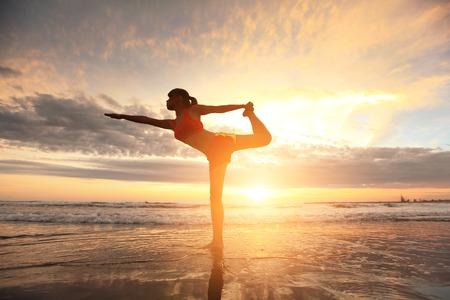 젊은 여성의 실루엣 석양 바다 해변에서 요가 연습 스톡 콘텐츠