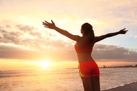 Smile Vrijheid en zorgeloos sport vrouw op het strand. Ze is genieten van serene oceaan natuur tijdens sport buiten. Aziatische schoonheid
