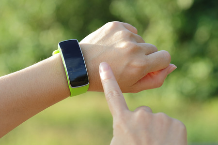 Smart watch on hand with empty screen on nature green background, screen is great for your design copy space