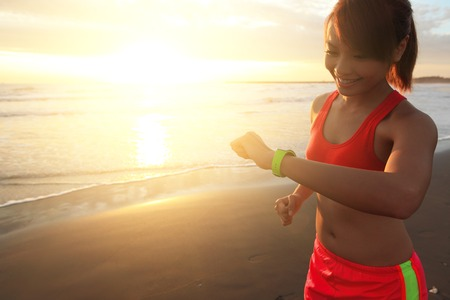 wearable: Health sport young woman run and look wear smart watch device with touchscreen on the beach at sunrise, asian
