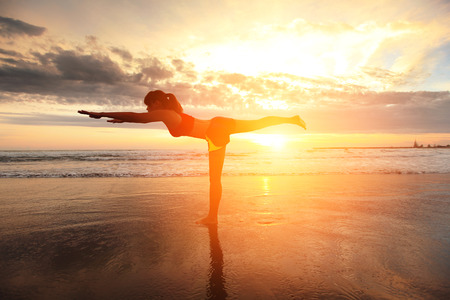 Sport Young woman silhouette practicing yoga on the sea beach at sunset photo