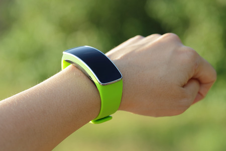 wearable: Smart watch on hand with empty screen on nature green background, screen is great for your design copy space
