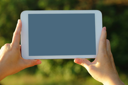 Using digital tablet pc with empty screen , nature green background, screen is great for your design copy space photo