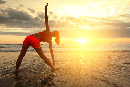 chinese woman: Sport Young woman silhouette practicing yoga on the sea beach at sunset