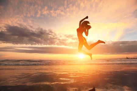 Šťastný skok sportovní mladá žena běží na pláži při východu slunce, asijských