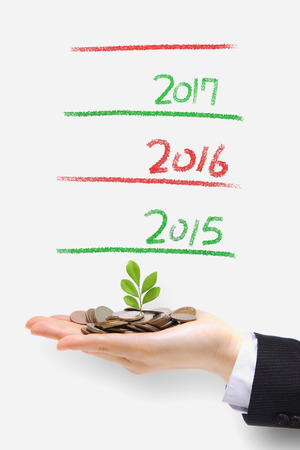 money tree grow up in 2015 new year - green plant sprouting from hand with money,concept for business and new year photo