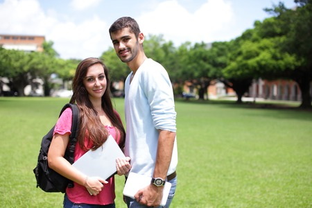 Happy College students smile to you on campus lawn, caucasian photo