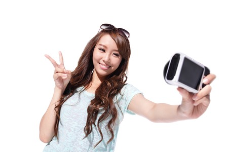 Happy travel young woman selfie taking pictures of herself isolated over white background, asian
