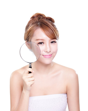 perfect face: young woman with perfect skin and magnifying glass check it isolated, concept for skin care, asian