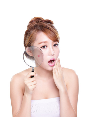 beauty skin: young woman with a acne and magnifying glass check it isolated, concept for skin care, asian