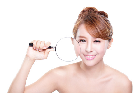 young woman with perfect skin and magnifying glass check it isolated, concept for skin care, asian photo