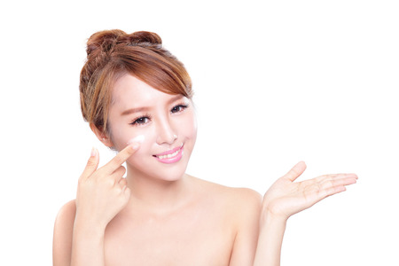 Portrait of young woman applying moisturizer cream on her pretty face isolated on white background, asian beauty photo