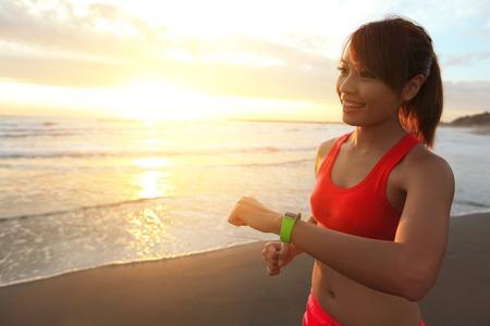 フィットネス: 健康スポーツの若い女性の実行と外観のタッチ スクリーンのスマートな腕時計デバイス、ビーチで着用日の出では、アジア