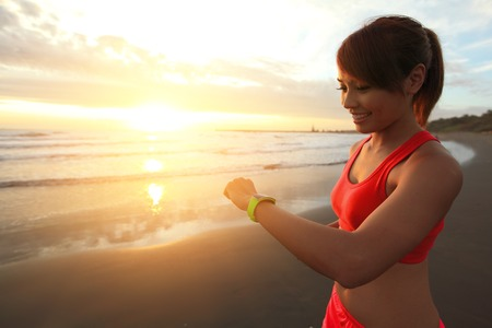 girl with a wristwatch: Health sport young woman run and look wear smart watch device with touchscreen on the beach at sunrise, asian