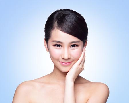 yeux: Belle femme soins de la peau du visage sourire � vous isol� sur fond bleu. Beaut� asiatique