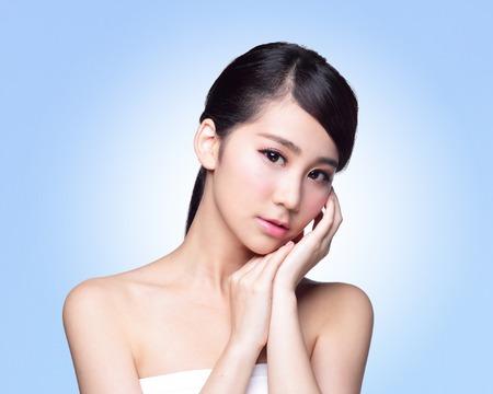 beauty wellness: Mooie Huid zorg vrouw geïsoleerd op een blauwe achtergrond. Aziatische schoonheid