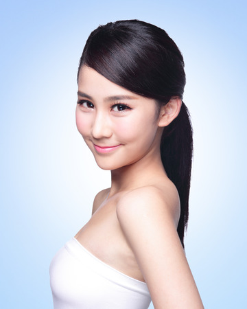 skin care: Beautiful Skin care woman Face smile to you isolated on blue background. asian Beauty