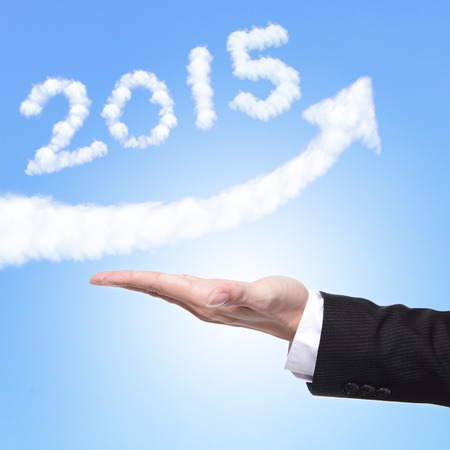 hand of Business man holding happy new year 2015 (white cloud and blue sky on sunny day) on his hand photo