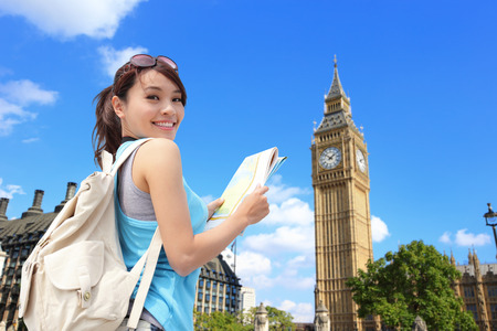 student travel: Happy woman travel in London with Big Ben tower, she look map and smile to you, asian