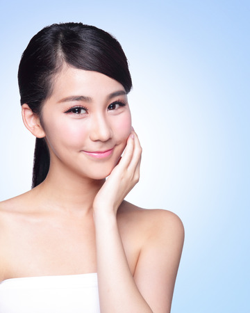 Bella cura della pelle donna faccia sorriso a voi isolato su sfondo blu. Bellezza asiatica Archivio Fotografico - 32499870