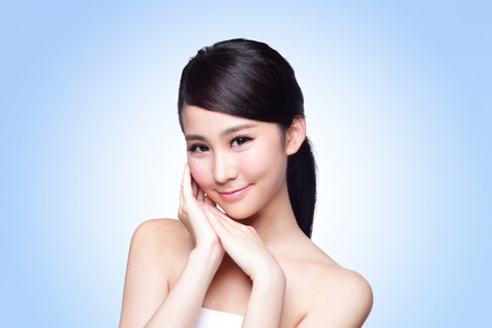 skin care woman: Beautiful Skin care woman Face smile to you isolated on blue background. asian Beauty