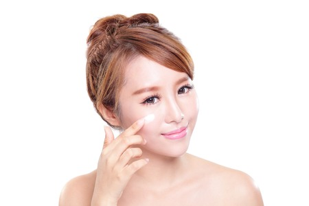 woman face cream: Portrait of young woman applying moisturizer cream on her pretty face isolated on white background, asian beauty