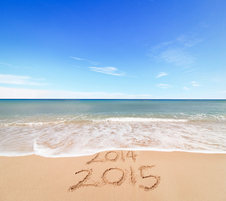 New Year 2015 is coming concept - inscription 2014 and 2015 on a beach sand, the wave is covering digits 2014 photo