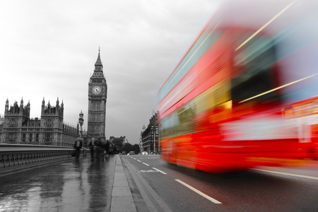 London, the UK. Red bus in motion and Big Ben, the Palace of Westminster. in retro monochrome style photo